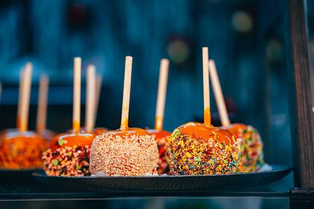Apples in caramel and sprinkles. Street food.
