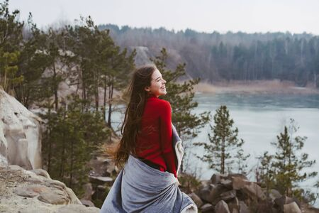 Young beautiful girl posing on a background of lake