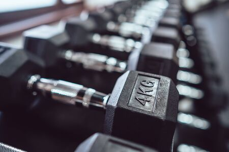 Close up many metal dumbbells on rack in sport fitness center.
