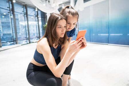 mother and girl using phone in gym for watching video Stock Photo - 125726938