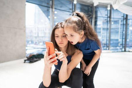 mother and girl using phone in gym for watching video Foto de archivo