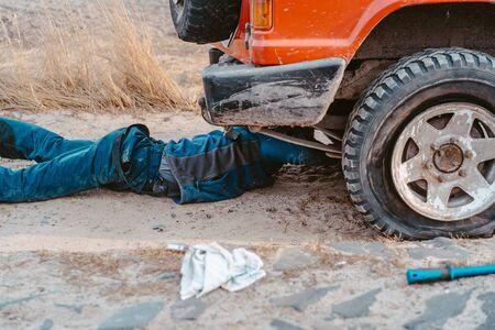man lies under a 4x4 car on a dirt road Stock Photo