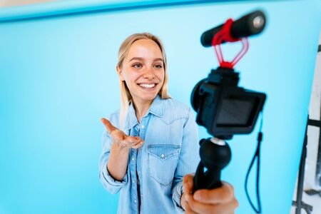 Beautiful girl blogger relieves itself at camera isolated blue background