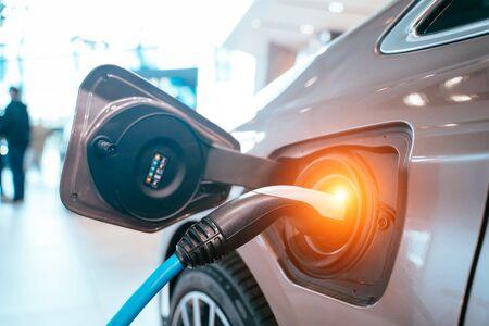 Fuente de alimentación enchufada a un coche eléctrico que se está cargando.