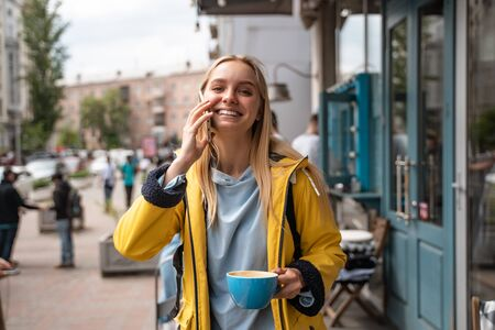 Enchanting blonde young woman with smartphone while on the street