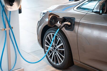 Power supply plugged into an electric car being charged. Banco de Imagens - 128854725