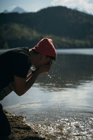 A man washes his hands on the shore of a forest lake Banco de Imagens