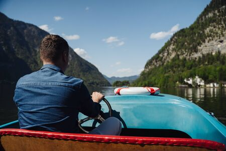 Handsome young guy controls a motorboat on a mountain lake, the mountains in the background Imagens
