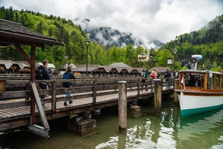 Scenic view on Konigssee Lake with wooden pier with moored touristic ship, great mountains canyon on background, Bavaria, Germany.