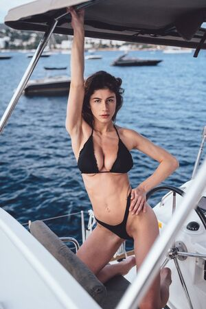 Photo extérieure de mode de belle jeune femme posant sur des yachts