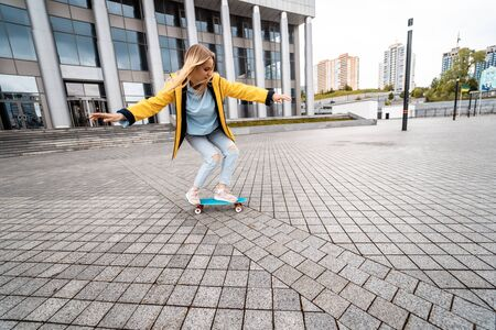 Blond female hipster woman riding on the longboard in the street at city. Фото со стока