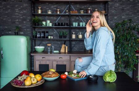Beautiful girl talking on the mobile phone in kitchen at home Stock Photo