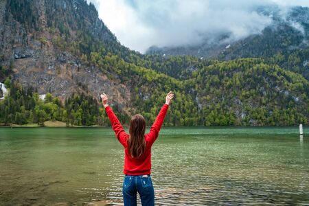 Beautiful young girl is raising his hands up against the backdrop of magnificent mountain lake Stockfoto