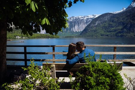 A couple in love travels. Honeymoon. Couple on a bench looking at the mountains.