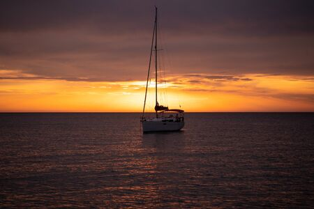 Aerial view from drone on boat shipping in sea, sunset. Yachting with a dramatic sunset as backdrop
