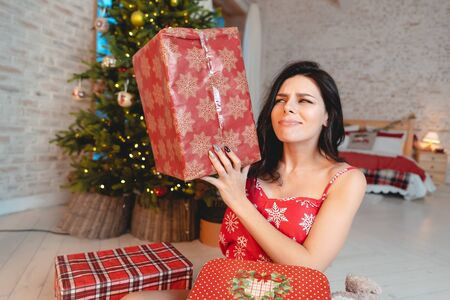 Beautiful young woman with gifts on the background of the Christmas tree Zdjęcie Seryjne