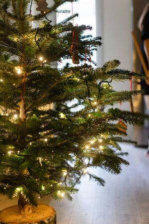 ジンジャーブレッドクッキーと花輪で飾られたクリスマスツリー 写真素材 - 132124940