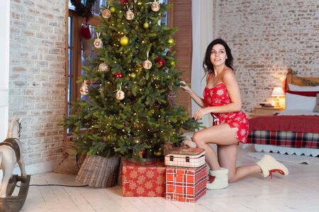Beautiful young woman standing by the tree