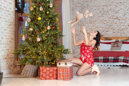 Beautiful young woman playing with a teddy bear by the Christmas tree Zdjęcie Seryjne