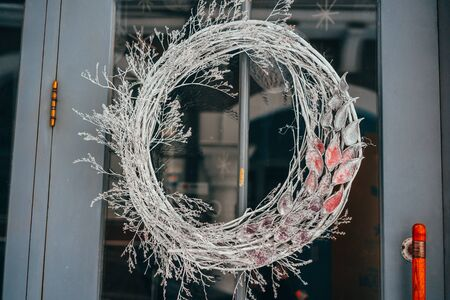 Christmas wreath hanging on the glass door in cafe Stock Photo