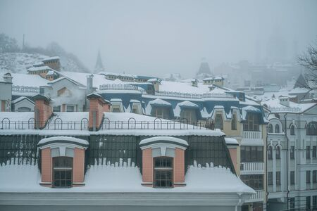 Copious snowfall over the city with the roofs