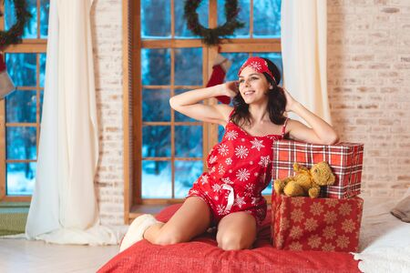 Beautiful woman in pajamas with gift box, window in the background. Banco de Imagens