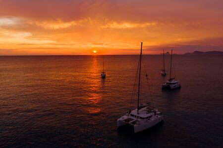 Aerial view from drone on boats shipping in sea, sunset. Yachting with a dramatic sunset as backdrop