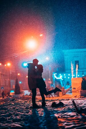 Young adult couple in each other's arms on snow covered street. Peaceful atmosphere in snowy winter night. Stock fotó