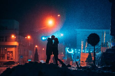 Young adult couple in each other's arms on snow covered street. Peaceful atmosphere in snowy winter night.