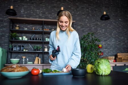 Young beautiful blonde takes on videos as she cooks in the kitchen