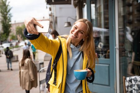 Enchanting blonde young woman with smartphone take selfie on the street Standard-Bild