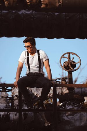 Guy in a shirt with suspenders posing at old pipes and valves