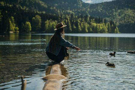 Young beautiful girl feeds a duck by the lake, mountains on the background Stock fotó