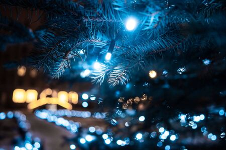 Christmas tree with cones on a city street illuminated with a garland. Close view