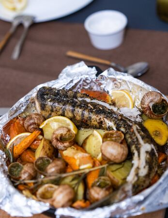 Grilled fish, sea snails with lemon and vegetables