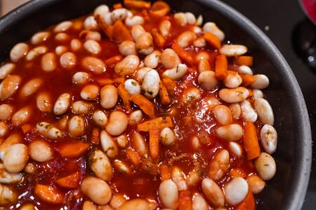 Carrots, garlic and beans with tomato sauce in a pan before cooking. Close veiw