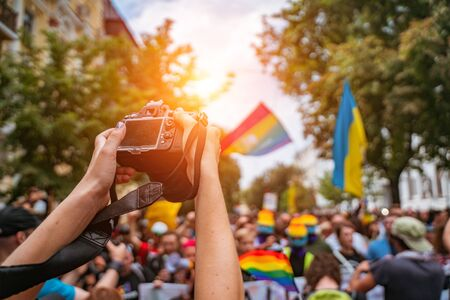 Correspondent takes photo during the Gay Pride parade. Holds the camera over the crowd