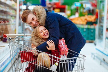 Il giovane bel ragazzo cavalca una ragazza in un supermercato in un carrello Archivio Fotografico