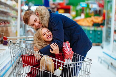 Young handsome guy rides a girl in a supermarket in a trolley Reklamní fotografie