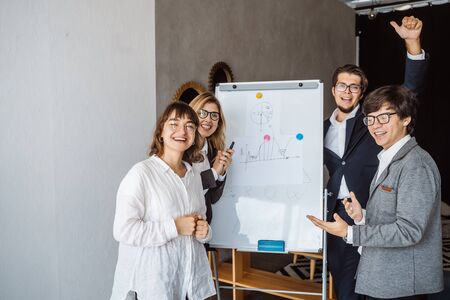 Businesspeople with whiteboard discussing strategy in a meeting Banque d'images