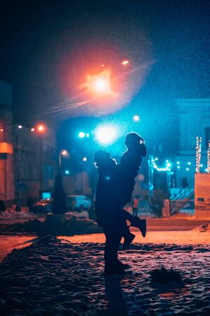 Young adult couple in each others arms on snow covered street. Stock fotó