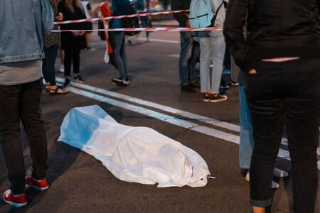 Human body covered by a sheet lying on the street.