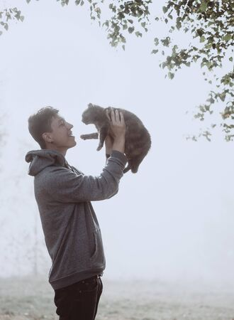 The guy holds a cat in the park. The park is shrouded in fog 版權商用圖片