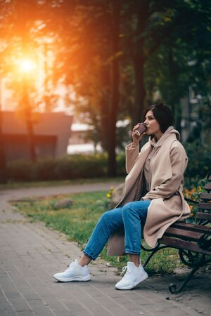 Beautiful young woman sitting on a bench drinking coffee enjoying in park Stok Fotoğraf