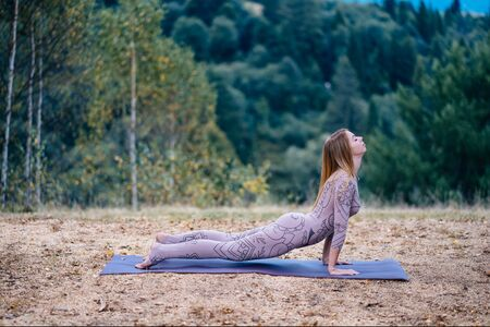A woman practices yoga at the morning in a park on a fresh air. Stok Fotoğraf