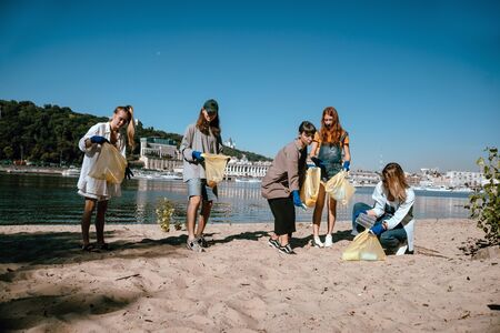 Group of activists friends collecting plastic waste on the beach. People cleaning the beach up, with bags. Stock Photo