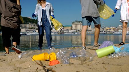 Group of activists friends collecting plastic waste on the beach. People cleaning the beach up, with bags. Standard-Bild - 139600262