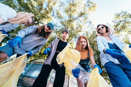 Group of activists friends throw a lot of garbage in a bag. Bottom-up shooting Stock Photo
