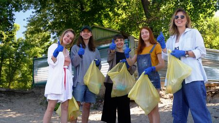 Group of activists friends collecting plastic waste on the beach. Environmental conservation. Stock Photo