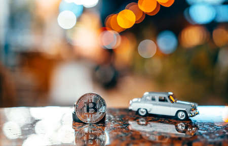 Silver bitcoin and Moskvich 401 on the table, glowing background
